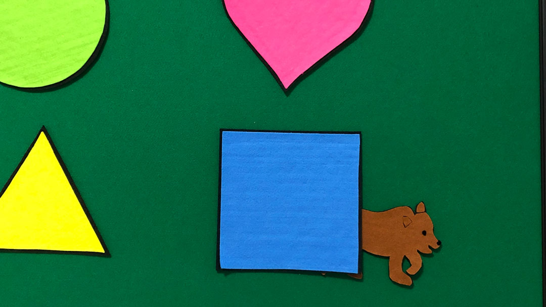 The bear is found behind the blue square while playing the shape game